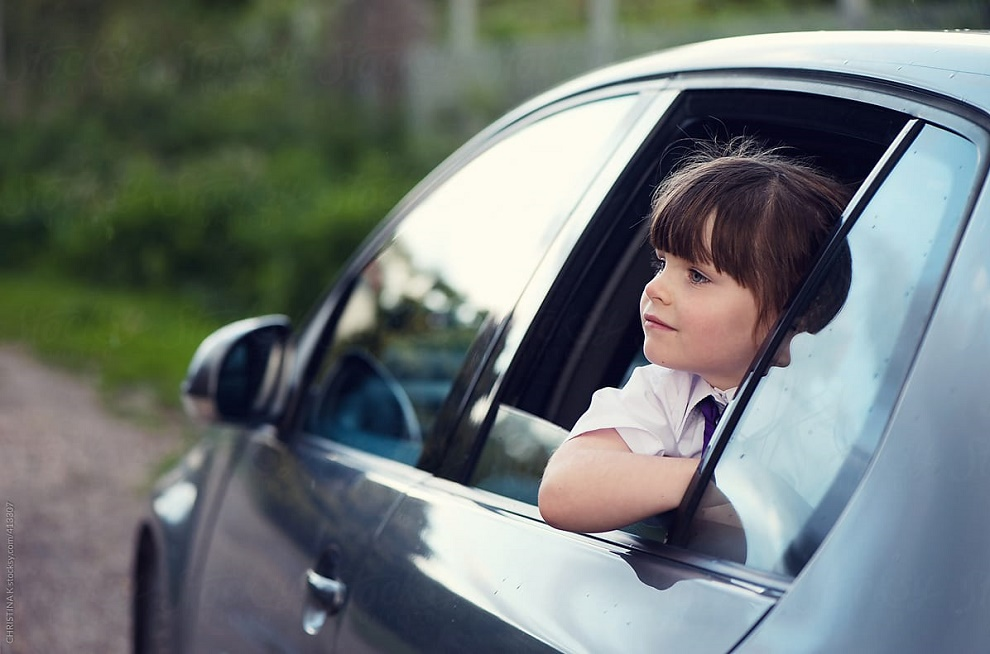 girl looking outside from car window